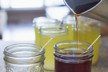 Pouring hot soy wax into glass jars