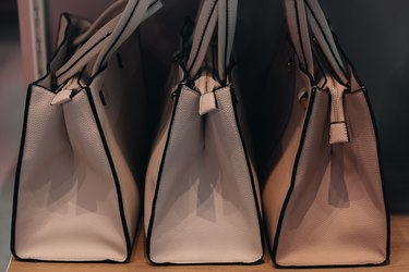 Beige handbags standing in a row.