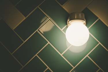 Round Light Fixture On Tiled Bathroom Wall With Copy Space