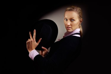 Magician moving her hat while performing against dark background with spotlight