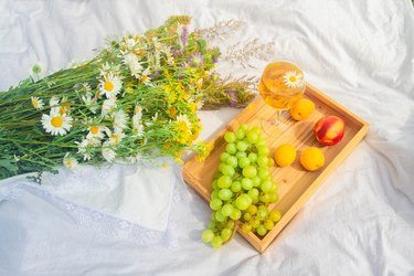 Outdoor recreation in the summer. Fruit and wine on a snow-white bedspread. Relax on a warm Sunny meadow