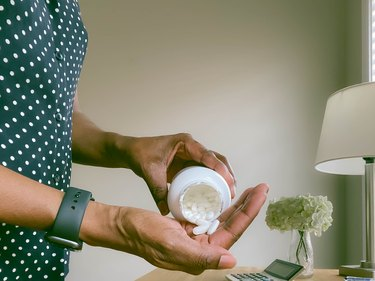 Woman pouring pills into palm of hand