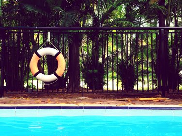 Life ring hanging on fence by swimming pool