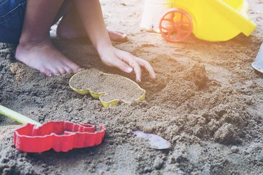 Girl playing with toys on sand