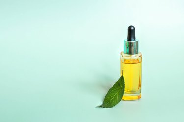 Glass bottle with cosmetic essential oil, fresh leaf isolated on green background. Organic natural product. Copy space.