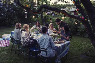 Multi-ethnic friends having food at dining table in yard