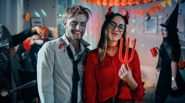 Halloween Costume Party: Brain Dead Zombie and Beautiful She Devil with Trident Pose as a Couple. In the Background Monsters Having Fun and Dancing in the Decorated Room