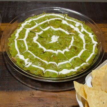 Guacomole topped with a sour cream spider web