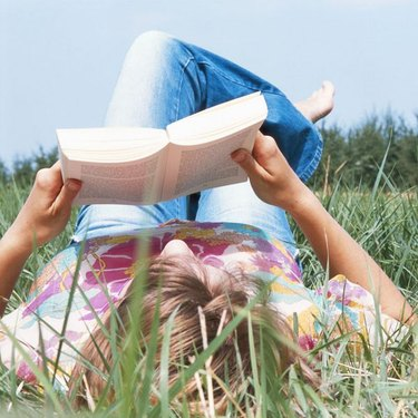 Young woman lying on field, reading book, ground view