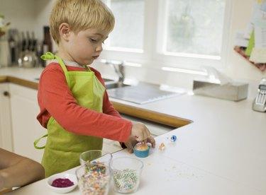 Boy decorating cupcake