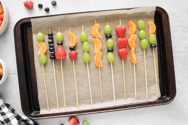 Insert skewer into pieces of fruit