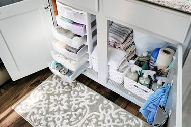 stackable storage bins under a kitchen sink