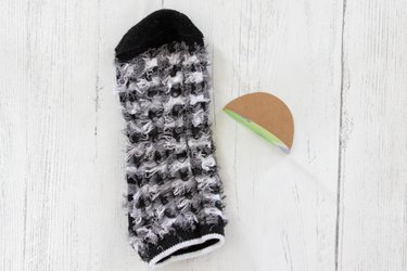 turn sock inside out and fold cardboard circle in half