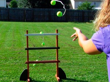 woman tossing tennis balls at ladder ball game
