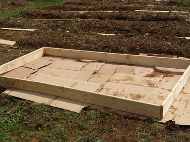 A simple wooden frame for a garden bed, made of four planks nailed together.