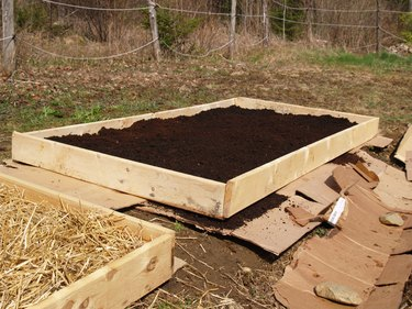 A framed-in garden bed filled with fresh soil.