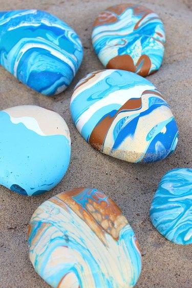 several paint pour rocks