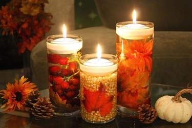 Fall floating candles with pumpkins and pine cones.