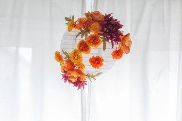 White hanging paper lantern with orange fall flowers.
