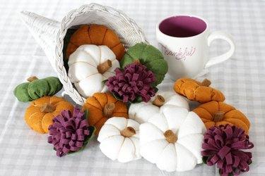 Wicker cornucopia filled with felt pumpkins.