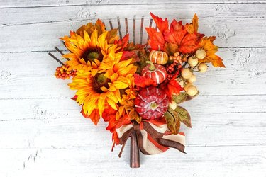 Fall door wreath with flowers and pumpkins.