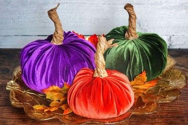 Jewel-toned velvet pumpkins on a gold plate