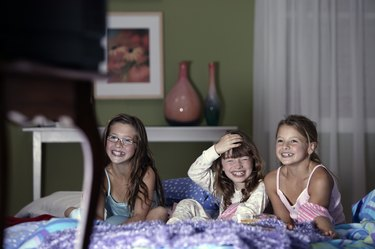 Girls watching television and laughing