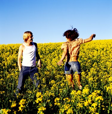 Young couple standing together in a field of flowers