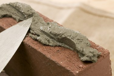 Close-up of brick spread with mortar by spade