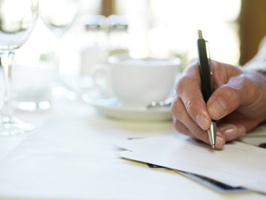 Man in restaurant, holding pen to paper, close-up of hand