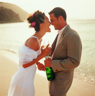 Bridal couple sharing champagne on beach