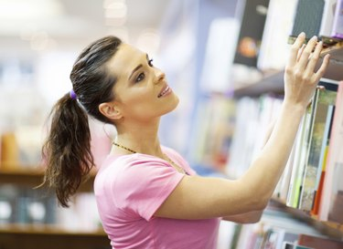 young woman searching for a book in bookstore