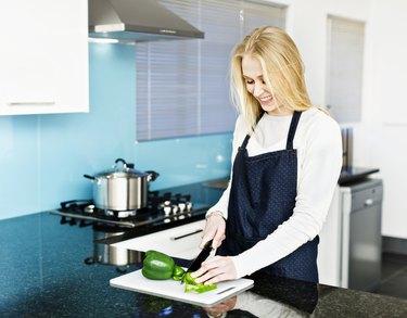 Pretty blonde smilingly prepares vegetables in modern kitchen