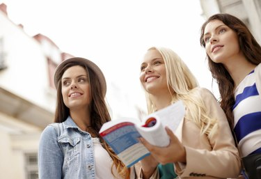 three beautiful girls with tourist book in city