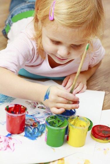 Cute little redhead girl painting.
