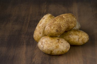 Raw Potatoes on Dark Wood Table