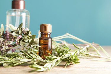 Bottle with aromatic oil and rosemary on a wooden table.