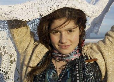 Portrait of teenage girl (16-17) holding shawl, smiling