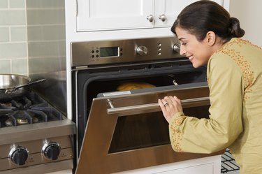 Woman checking on Thanksgiving turkey in oven