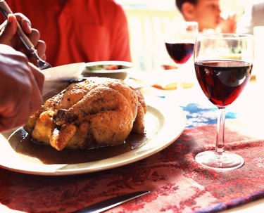 Hands carving roast chicken