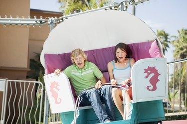 Couple riding amusement park ride