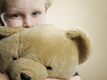 Portrait of a 6 year old boy hugging teddy bear