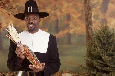 Man in pilgrim costume holding corn