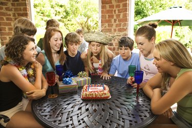 Teenage girl blowing out candles on birthday cake at party