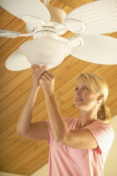 Woman Adjusting Ceiling Fan