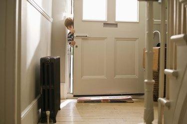 Boy sneaking in door