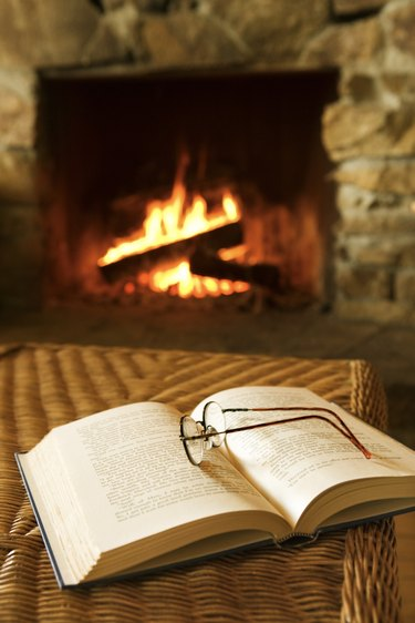 Glasses and book near fireplace