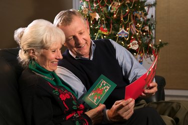 A mature couple enjoy and share Christmas cards near their decorated tree.