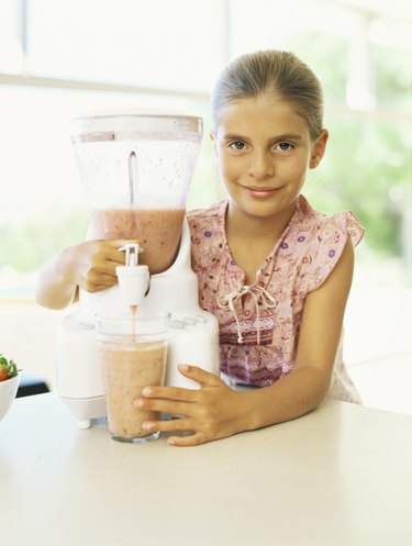 Portrait of a girl pouring a smoothie from a juicer