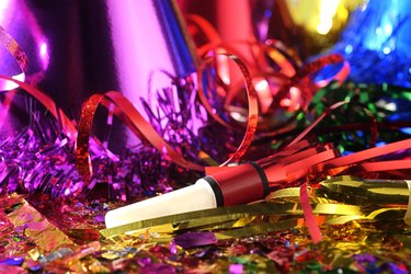 Close-up still life of New Year's Eve party favors including hats and noise makers.